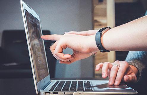O futuro do mercado de trabalho. Imagem mostra um notebook, uma pessoa apontando para o notebook e outra usando o touch do computador